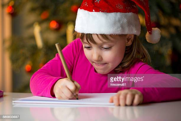 Little girl with Christmas cap writing a Christmas list