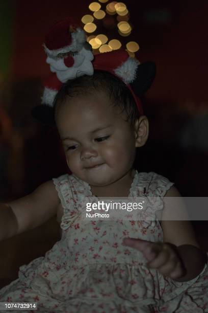 A little girl with Christmas tree and sprinkles of lights in the background on December 24 2018 in Pekanbaru Indonesia