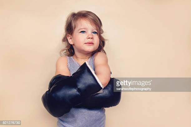 Little girl with confident expression wearing boxing gloves