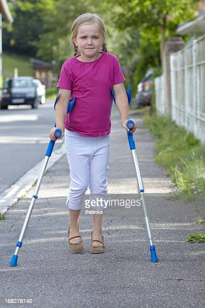 little girl with crutches - crutches stock photos and pictures