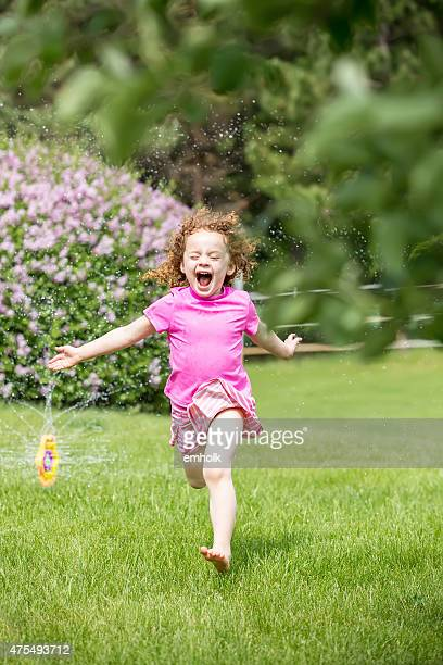 Little Girl With Curly Red Hair Running Through Sprinkler