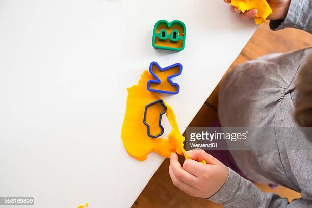 Little girl with cutters and yellow modeling clay