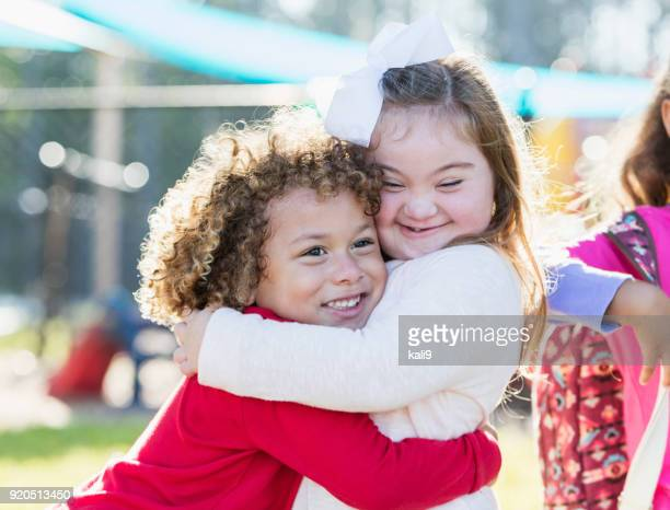 little girl with down syndrome and boy hugging - down syndrome stock pictures, royalty-free photos & images
