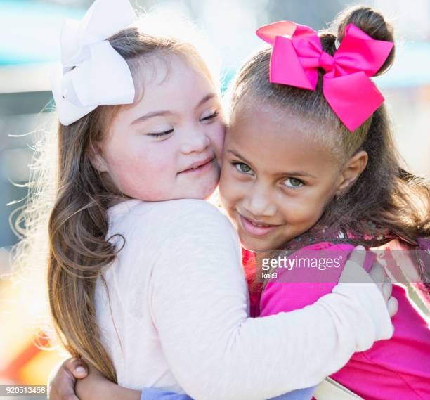 Little girl with down syndrome and friend hugging