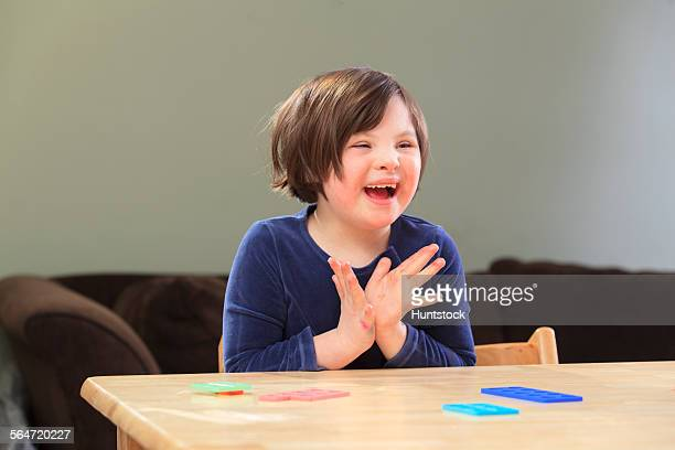 Little girl with Down Syndrome playing a learning game and smiling