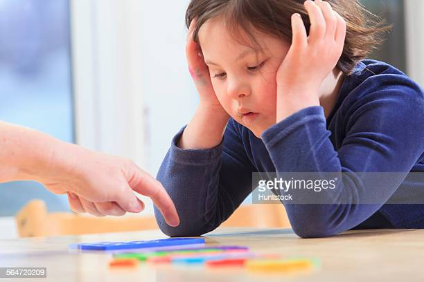 little girl with down syndrome playing a learning game with her mom - discapacidad intelectual fotografías e imágenes de stock