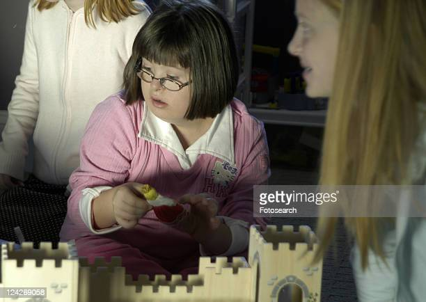 little girl with down syndrome playing with a castle. - autism spectrum disorder stock photos and pictures
