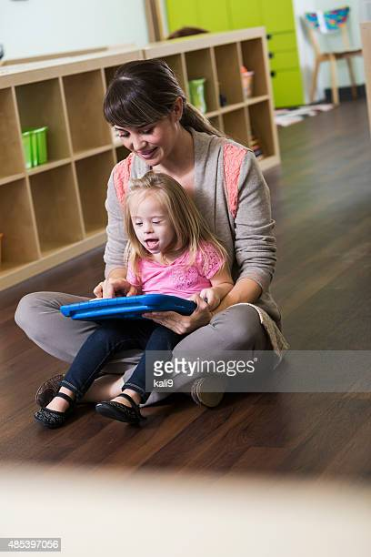 Little girl with down syndrome sitting on teacher's lap