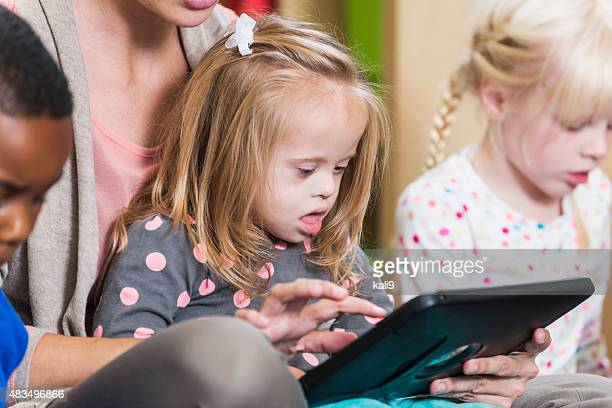 Little girl with down syndrome watching digital tablet