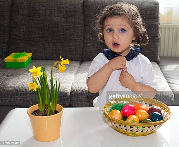 Little girl with Easter egg basket and flowers