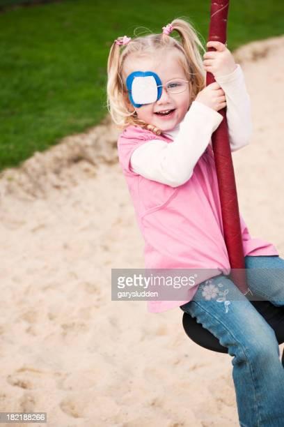 little girl with eye patch having fun