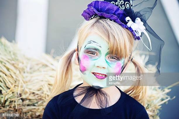 Petite fille avec peinture visage fantaisie sorcière pour Halloween