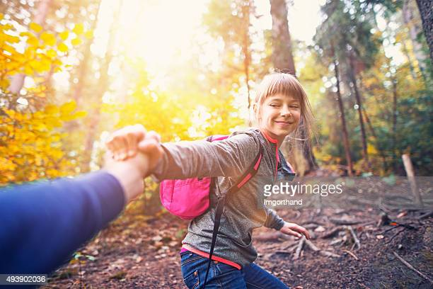 Little girl with father hiking in autumn forest