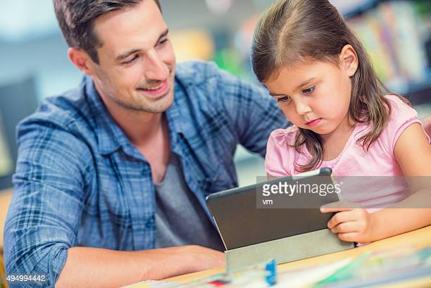 Little girl with father using digital tablet