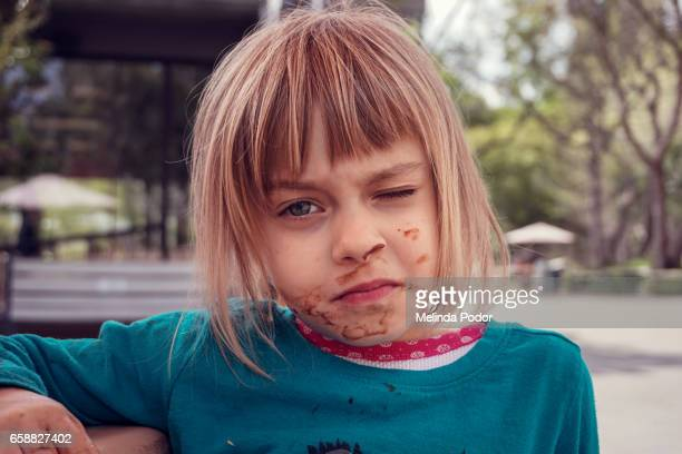 Little girl with food on her face, grimacing