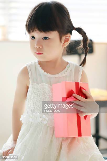 little girl with gift box - little girls giving head stock photos and pictures