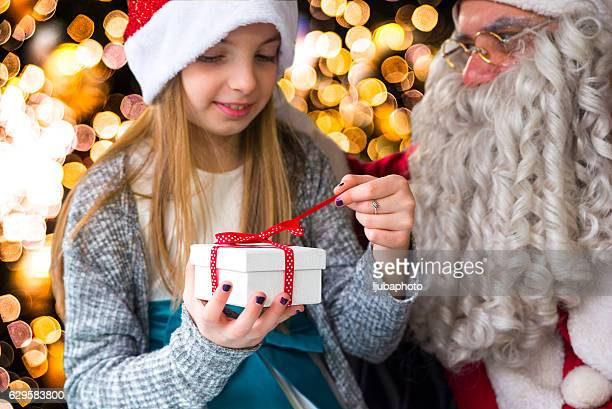 Little Girl with gift next to Santa Claus