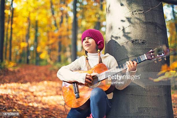 Niña con guitarra en el bosque de otoño.