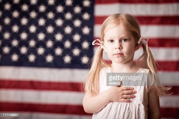 Little Girl with Hand on Heart by American Flag