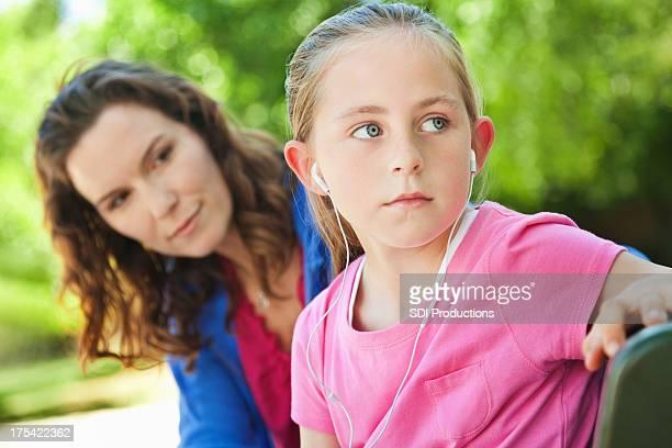 Kleines Mädchen mit Kopfhörern ignorieren Mutter