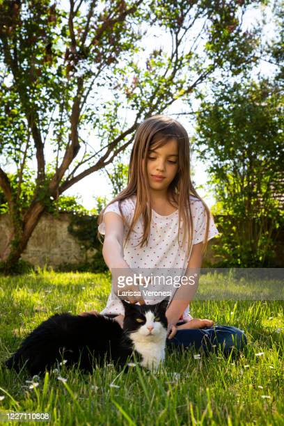 little girl with her cat on a meadow - larissa veronesi stock pictures, royalty-free photos & images