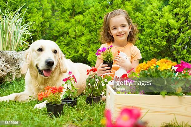 Little girl with her dog gardening.