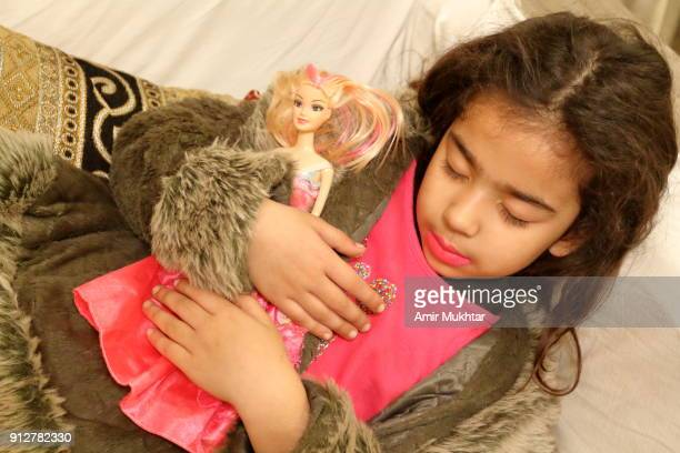 little girl with her doll - amir mukhtar stock photos and pictures