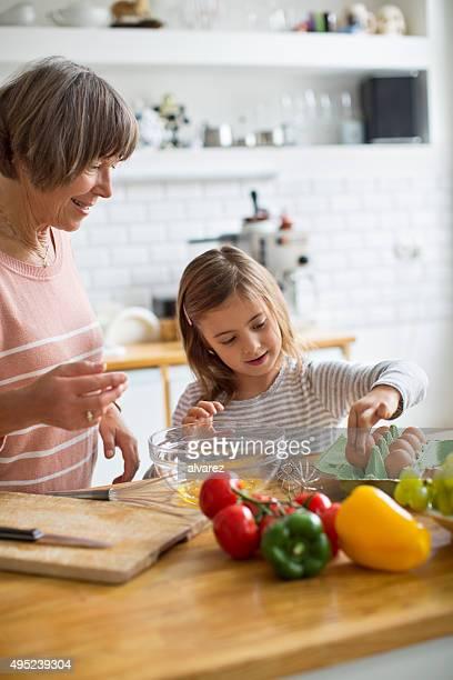 Petite fille avec sa grand-mère, préparer les repas