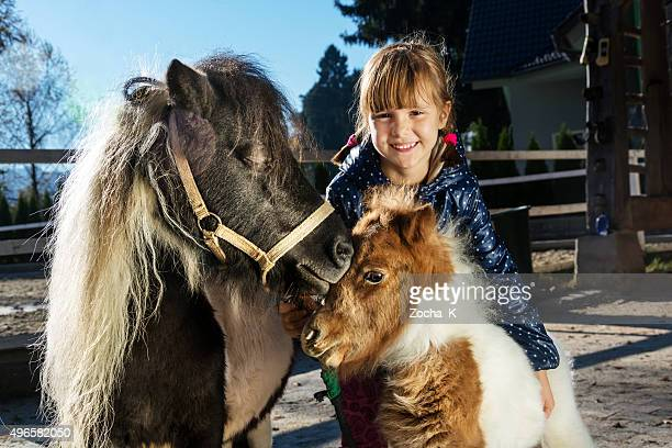 Little girl with her pony pets - mare and foal
