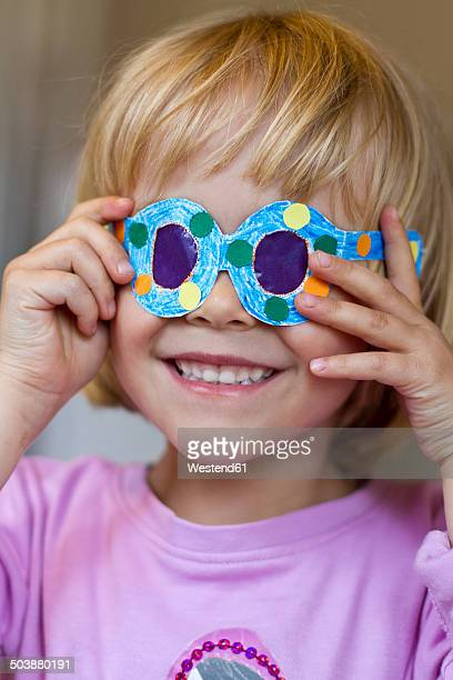 Little girl with her selfmade paper glasses