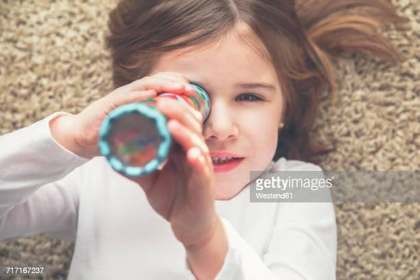 Little girl with kaleidoscope lying on the carpet
