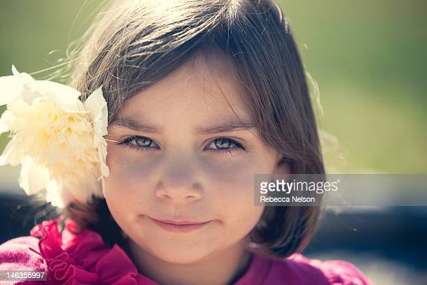 little girl with large peony flower behind her ear - rebecca nelson stock pictures, royalty-free photos & images