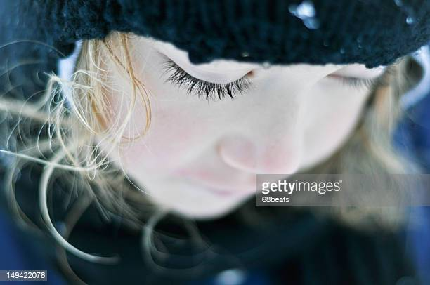 Little girl with long dark lashes looking down