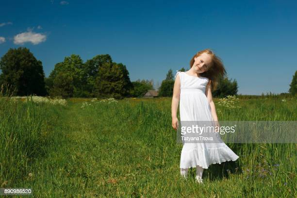 little girl with long hair in a white dress on a summer field with wildflowers - long dress - fotografias e filmes do acervo