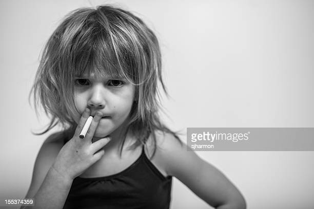 little girl with messy hair holds cigarette, looks at camera - emphysema stock photos and pictures