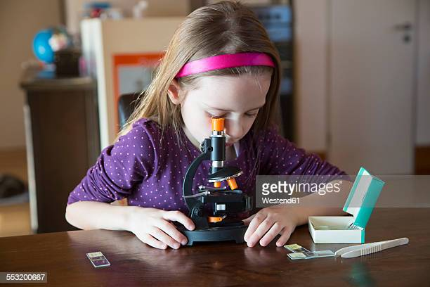 Little girl with microscope at home