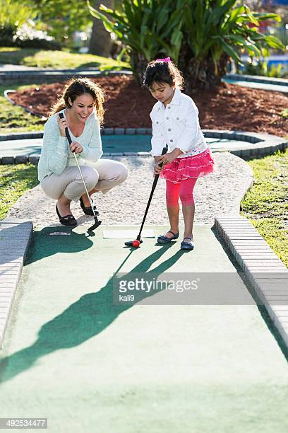 Little girl with mother playing miniature golf