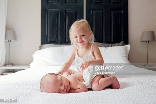 Little girl with newborn baby on bed