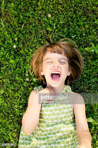 Little girl with open mouth and closed eyes lying on a meadow