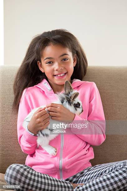 little girl with pet rabbit - hairy girl stock pictures, royalty-free photos & images
