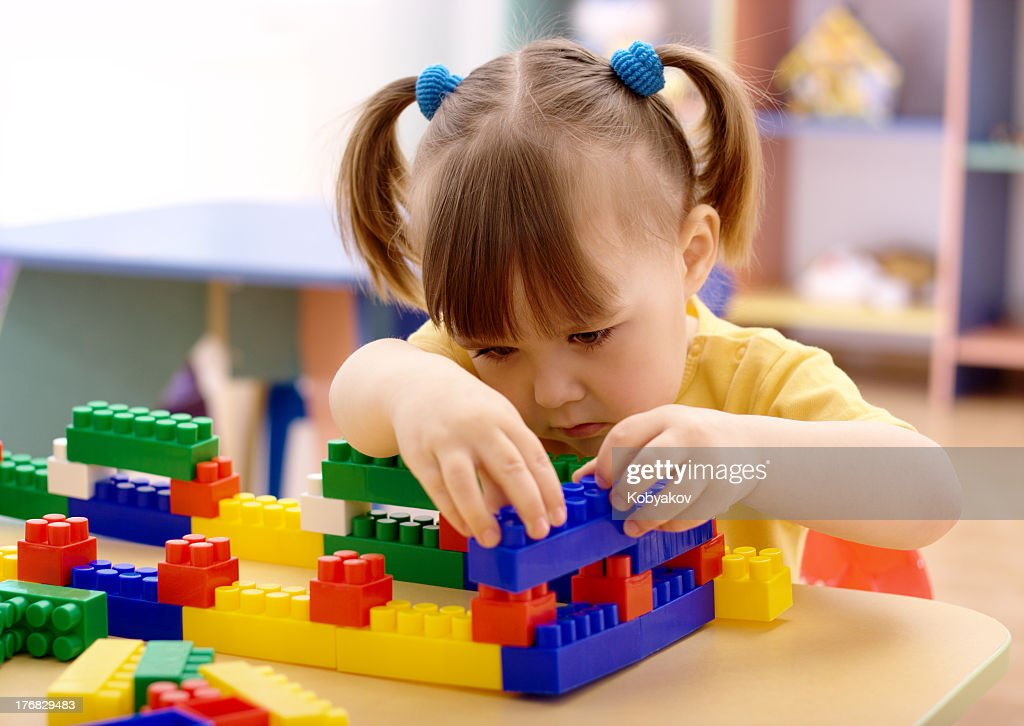 Little girl with pig tails playing with plastic blocks at her seat : Stock Photo