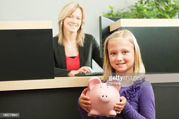 Kleines Mädchen mit Sparschwein auf Teller Bar