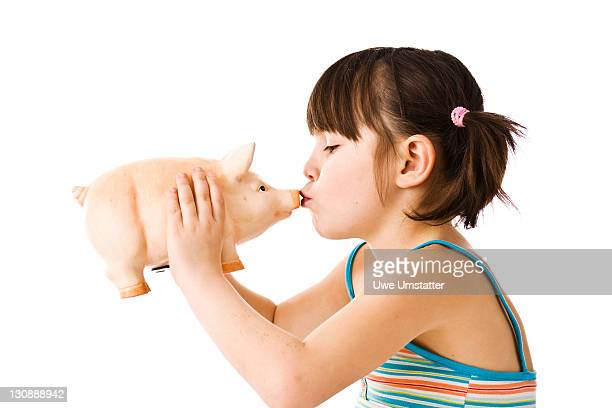 Little girl with pigtails kissing a piggy bank