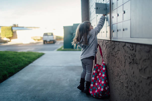 Little girl with pink bag opens door to apartment cluster mailbox
