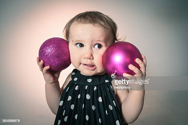 little girl with pink christmas baubles - heshphoto photos et images de collection