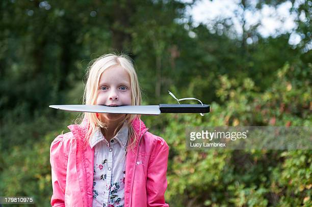 Little girl with plastic knife in her mouth
