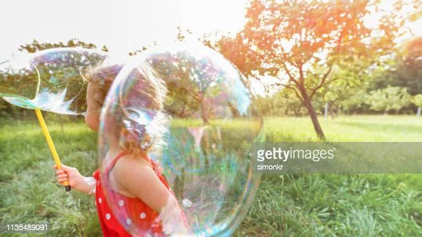 kleines mädchen mit seifenblase im park - innocence stock-fotos und bilder