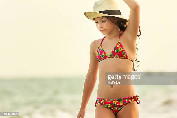 little girl with straw hat walking at the beach - young tiny girls stock photos and pictures