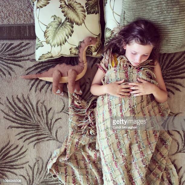 little girl with stuffed animal dinosaur napping - carré composition photos et images de collection