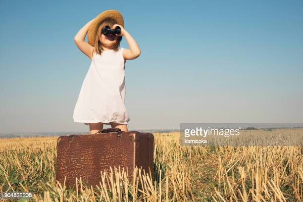 Little girl with suitcase is looking trough binoculars